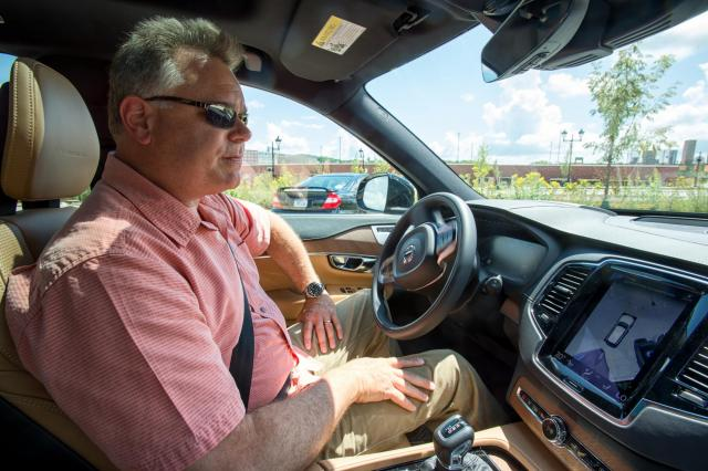 man in driver seat of car with hands off the wheel demonstrating driverless car technology