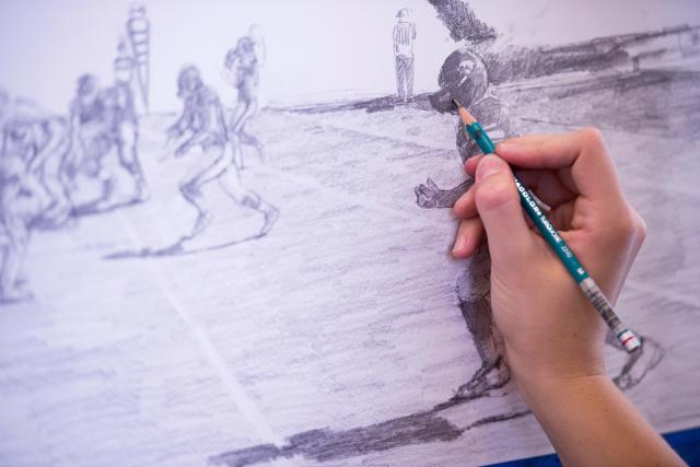 artist working on drawing of football game