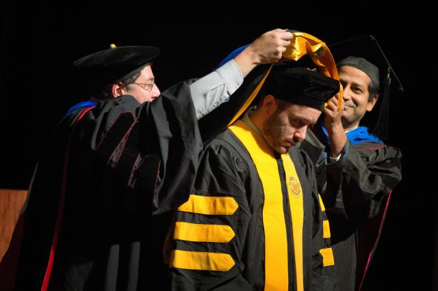 A University of Iowa student receives his degree during the Graduate College commencement ceremony Dec. 16 at Hancher Auditorium. About 250 students received degrees at the ceremony.