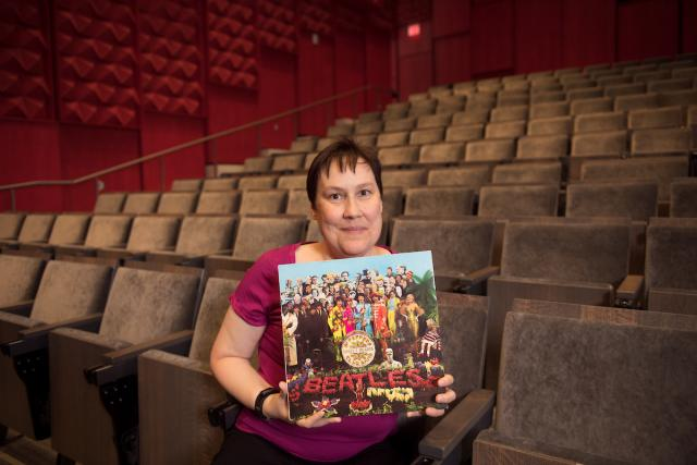 woman in theater holding album