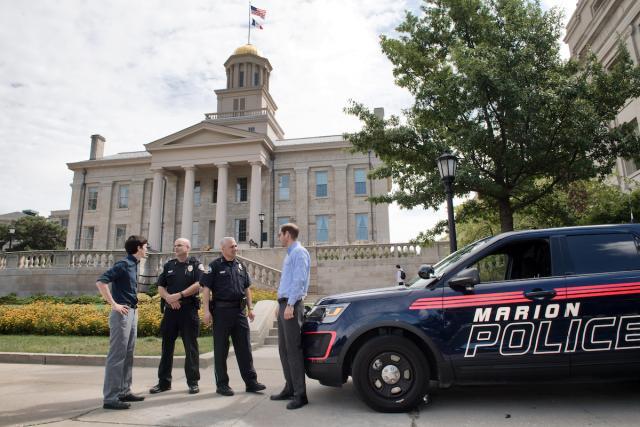 men speaking near police car in front of ol capitol