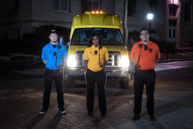 ui public safety members in front of nite ride vehicle