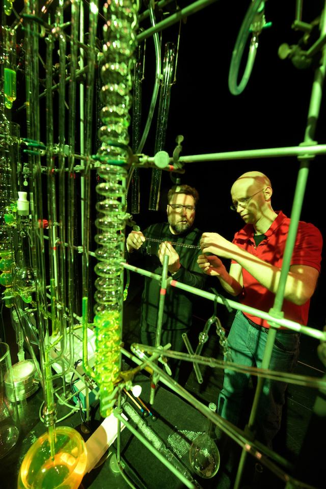 two men work with chemistry instruments used in performance