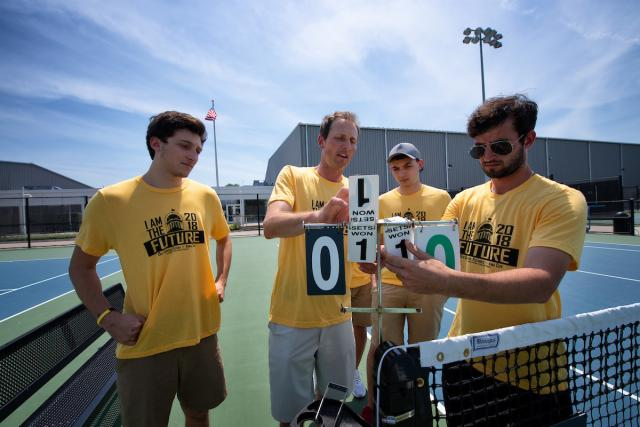 University of Iowa students and an instructor get a tennis scoreboard ready for an upcoming tournament