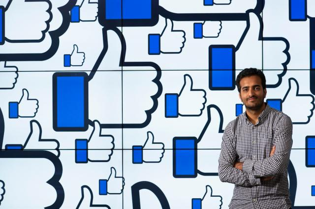 Shehroze Faroogi standing before wall of Facebook like graphics