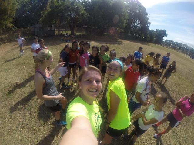 Soccer players take a selfie with kids.