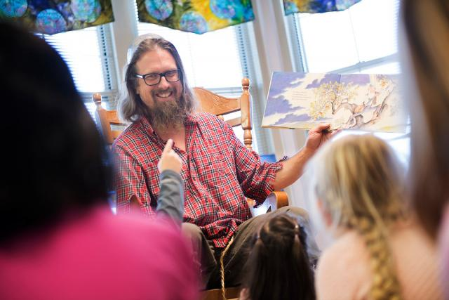 arborist andy dahl, dressed as johnny appleseed, reads to children