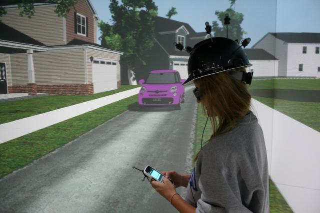 woman using smartphone while at a crosswalk with oncoming traffic in a simulation environment