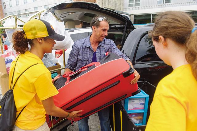 Student volunteers help man move luggage.