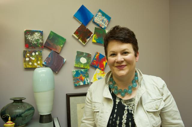 woman posing for portrait with small paintings in background