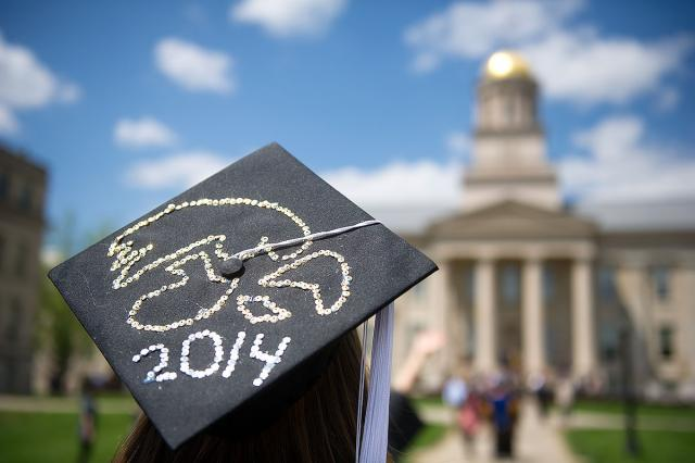 Graduation cap with tigerhawk and 2014 decorated on it, in front of Old Capitol