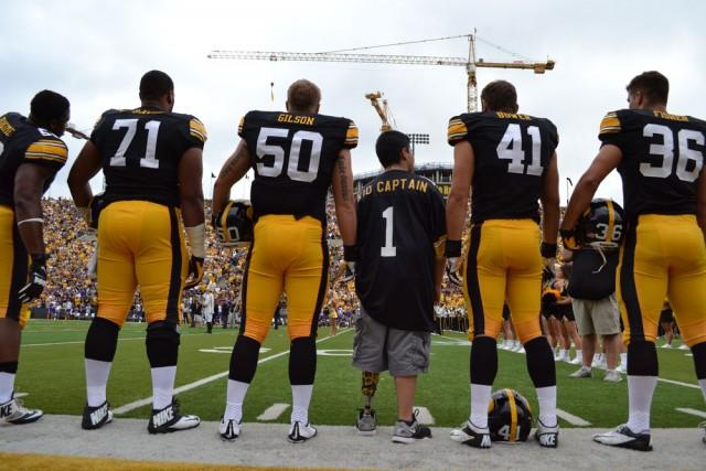 Kid captain standing with UI Hawkeye football players