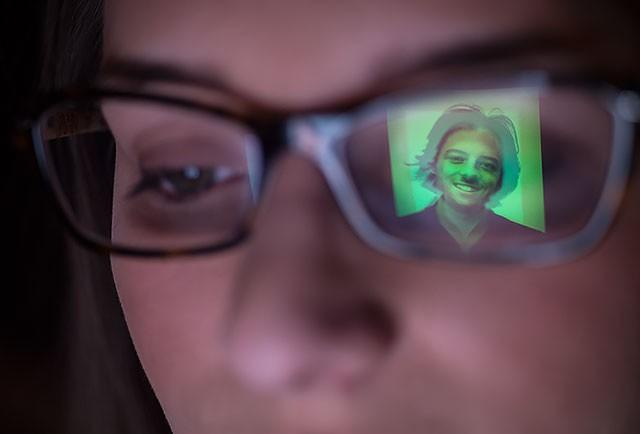 A dating profile picture reflected in a viewer's glasses
