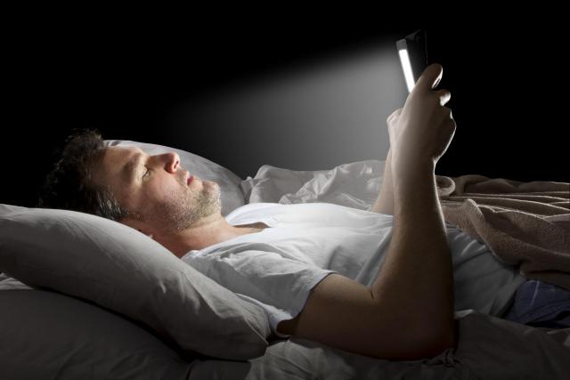 man lying in bed using a tablet device