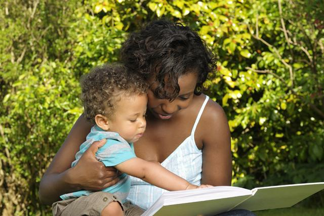 Mother reading a book to her young child