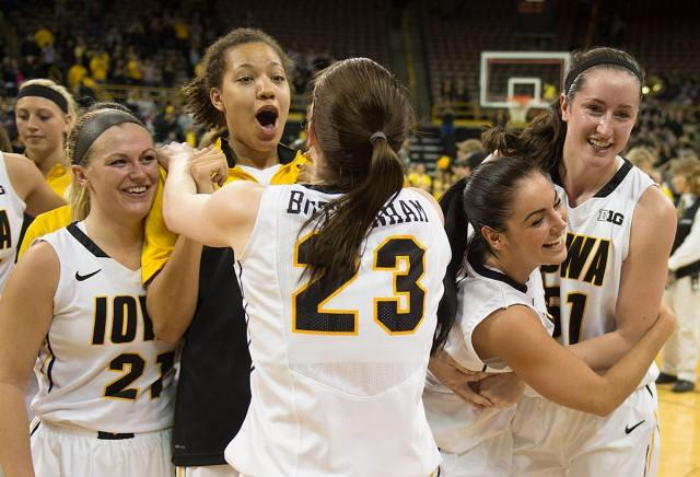 Members of the women's basketball team jump and hug on the court after a victory.