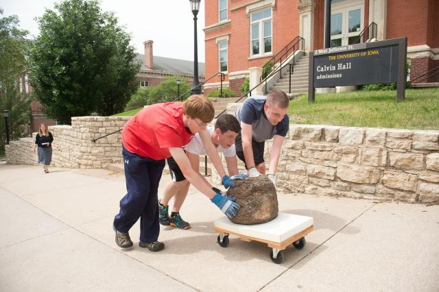 students pushing coal ball on cart