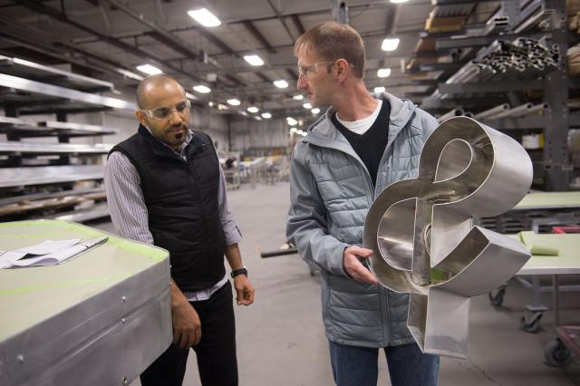 two men, one of whom is holding an ampersand
