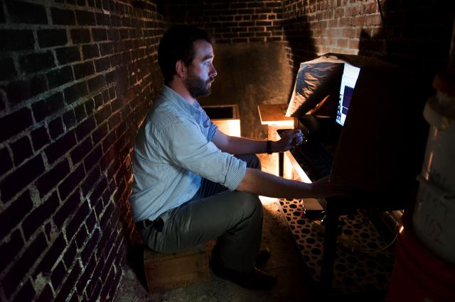 man monitoring seismometer in basement room
