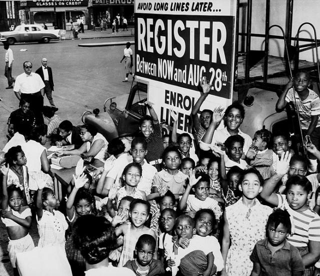 African-American children gather around a voter registration booth in the early 1960s