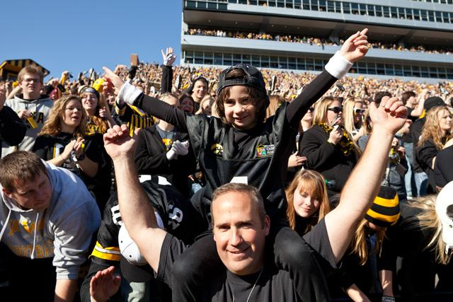 Kid-captain Kali Buchanan sitting on her dad's shoulders, cheering in the crowd at Kinnick.