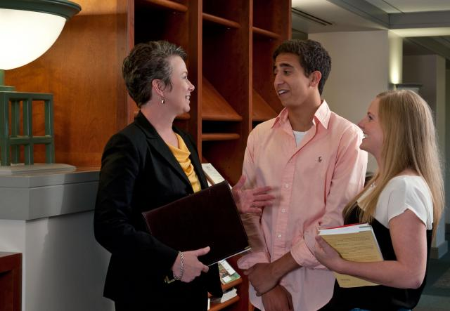 Dean Sarah Fisher Gardial in the Pomerantz Business Library with undergraduate students Faisal Alabsi and Sarah Pedigo.