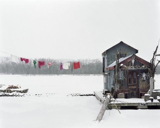 A photograph of a houseboat and a clothesline on the Mississippi River in the winter.
