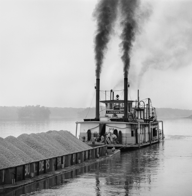 A photograph of a towboat pushing a barge on a river