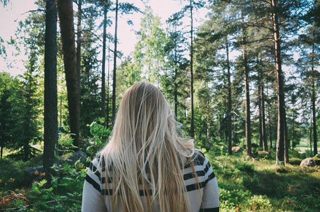 a girl walks through a forest in Sweden