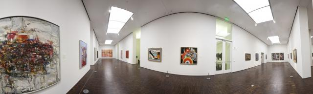 A wide angle photograph of works of art in a museum
