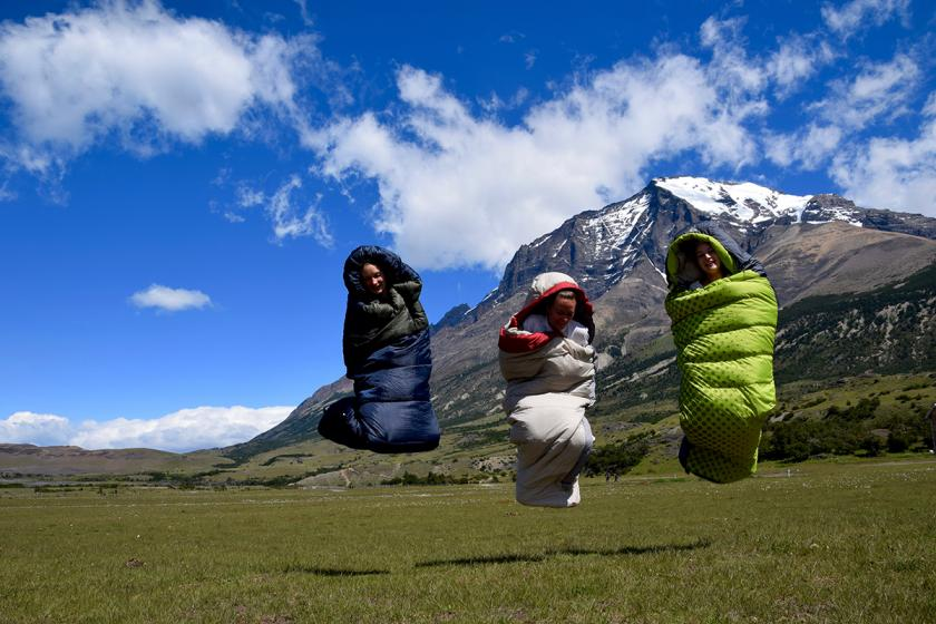 bundled hikers jumping