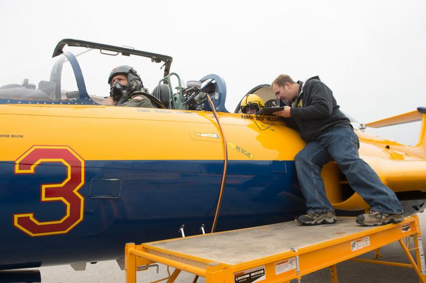 two men sitting in jet while third man checks equipment