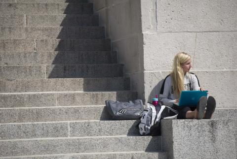 student studying on Old Capitol steps