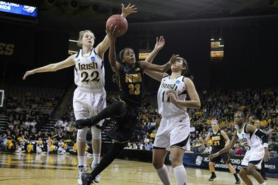 Women's basketball player driving to the basket