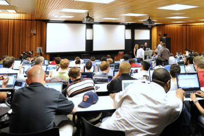 Male business students watching a presentation