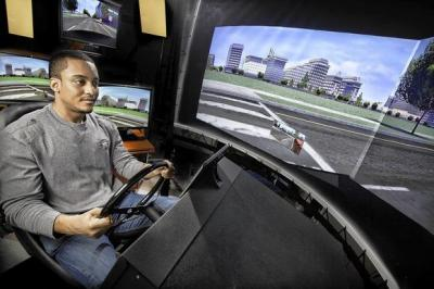 A man drives a vehicle in the UI's National Advanced Driving Simulator