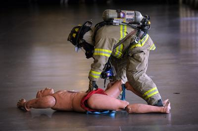 "A firefighter examines a ""dummy"" victim."