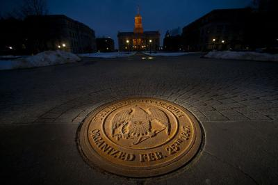 Old cap at night with university seal in the foreground.