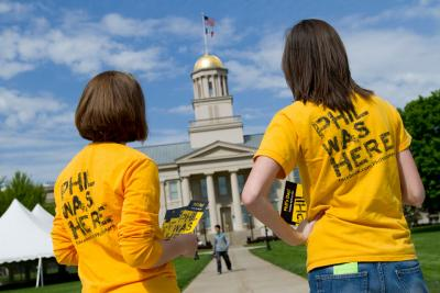 people wearing Phil Was Here shirts stand near Old Capitol