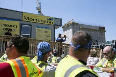 Wycliffe Gordon plays trombone as construction workers eat lunch at the Hancher Auditorium site on the University of Iowa campus in Iowa City on Wednesday, May 21, 2014.