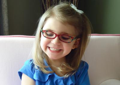 young girl wearing red glasses, smiling