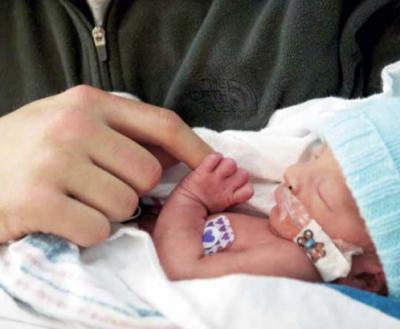 a photo of a premature baby holding someone's finger at UI Health Care