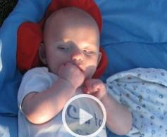 a screen shot of a video that has a baby sucking its hand