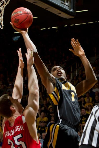 Iowa basketball player Melsahn Basabe (1) reaches for a layup with the ball in his extended right hand as Dayton player Matt Kavanaugh (35) attempts to block, but is too low.