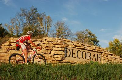 cyclist by Decorah city sign