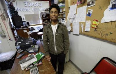 Ngun Za Bik stands at the front counter of his Grace Chin Store that once housed a pizza restaurant, in Columbus Junction, Iowa, on Wednesday, April 17, 2013.  AP Photo by Charlie Neibergall