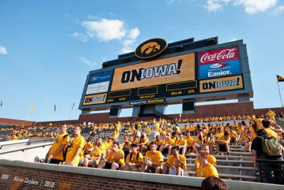 Students sitting in stands at Kinnick Stadium during On Iowa celebration