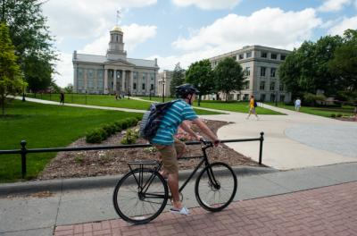 A student rides a bike across campus in front of the UI Pentacrest.