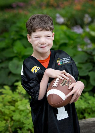Carson Thomas standing infront of a garden wearing a hawkeye jersey and holding a football.