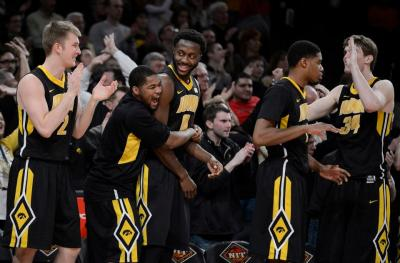 Men's basketball players celebrate a victory over Maryland